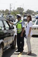Israel Police and volunteers distibuting information to car (...)